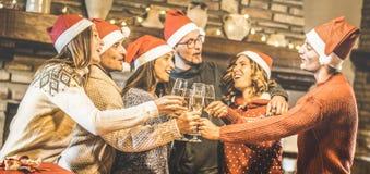 与圣诞老人帽子的朋友小组庆祝圣诞节用香槟酒的在家敬酒晚餐-寒假概念 库存图片