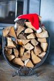 与圣诞老人帽子的木柴在a附近的房子里 免版税库存照片