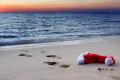 与圣诞老人帽子的海滩在日落 免版税库存照片