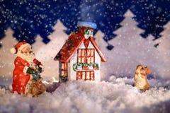 与圣诞老人的圣诞节图片和一个兔宝宝在房子冬天夜附近 免版税库存照片