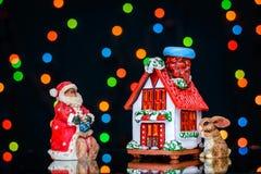 与圣诞老人的圣诞节图片和在房子附近的一个兔宝宝色的光背景的  免版税库存图片