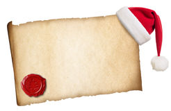 与圣诞老人的帽子和蜡封印的老羊皮纸 库存图片