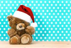 与圣诞老人的帽子的玩具熊 圣诞节装饰装饰新家庭想法 库存照片