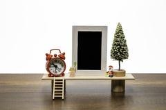 与圣诞老人的空白的黑照片与圣诞树和红色闹钟的框架和天使 库存图片