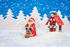 与圣诞老人的美丽的圣诞卡和一个房子在雪的冬天森林里 库存图片