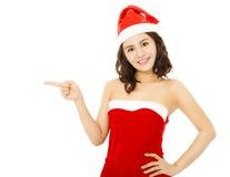 与圣诞老人盖帽的微笑的少妇佩带的圣诞节衣服 库存图片