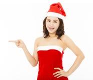 与圣诞老人盖帽的愉快的少妇佩带的圣诞节衣服 免版税库存图片