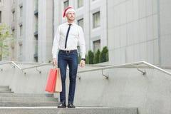 与圣诞老人红色帽子的成功年轻成人姜商人,看起来去和拿着礼物 库存图片