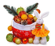 与圣诞老人袋子、圣诞节中看不中用的物品和白色玩偶兔子的新年构成在黄色礼服 免版税库存图片