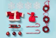与圣诞老人` s夹克,袋子,棒棒糖,雪花,在蓝色的sleid的圣诞节汇集 平的位置 顶视图 免版税库存照片