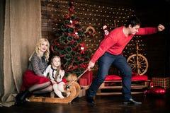 与圣诞节冬天雪橇的美丽的愉快的家庭在新年的装饰内部与欢乐圣诞树和C的 图库摄影