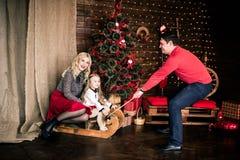 与圣诞节冬天雪橇的美丽的愉快的家庭在新年的装饰内部与欢乐圣诞树和C的 库存图片