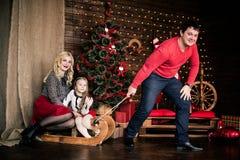 与圣诞节冬天雪橇的美丽的愉快的家庭在新年的装饰内部与欢乐圣诞树和C的 免版税库存照片