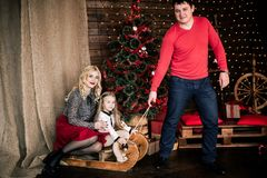 与圣诞节冬天雪橇的美丽的愉快的家庭在新年的装饰内部与欢乐圣诞树和C的 库存照片