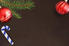 与圣诞节冷杉分支、棍子和红色和波浪球的黑暗的背景 免版税库存照片