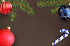 与圣诞节冷杉分支、棍子,红色波浪和蓝色球的黑暗的背景 免版税图库摄影