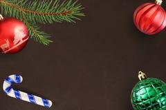 与圣诞节冷杉分支、棍子,红色波浪和绿色有肋骨球的黑暗的背景 库存照片