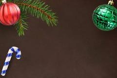 与圣诞节冷杉分支、棍子,红色波浪和绿色有肋骨球的黑暗的背景 免版税库存图片