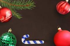 与圣诞节冷杉分支、棍子,红色波浪愚钝和绿色有肋骨球的黑暗的背景 库存照片