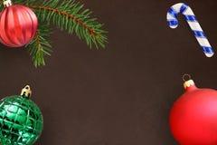 与圣诞节冷杉分支、棍子,红色波浪愚钝和绿色有肋骨球的黑暗的背景 免版税库存照片