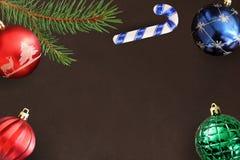 与圣诞节冷杉分支、棍子,红色波浪,蓝色和绿色球的黑暗的背景 免版税图库摄影