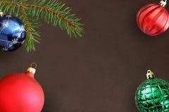 与圣诞节冷杉分支、蓝色,绿色有肋骨和红色波浪球的黑暗的背景 免版税库存图片