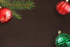 与圣诞节冷杉分支,红色波浪和绿色有肋骨球的黑暗的背景 免版税库存照片