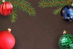与圣诞节冷杉分支,红色波浪愚钝,绿色和蓝色球的黑暗的背景 免版税图库摄影