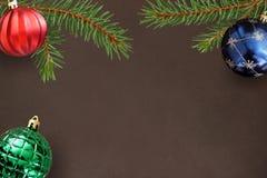 与圣诞节冷杉分支,红色波浪,蓝色和绿色球的黑暗的背景 库存照片