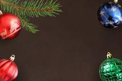 与圣诞节冷杉分支,红色波浪,蓝色和绿色球的黑暗的背景 免版税库存图片