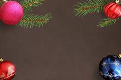 与圣诞节冷杉分支,红色,波浪,桃红色,蓝色球的黑暗的背景 库存照片