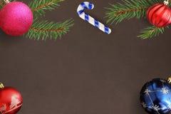 与圣诞节冷杉分支,红色,波浪,桃红色,蓝色球,棍子的黑暗的背景 免版税库存图片