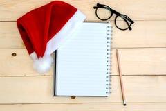 与圣诞节帽子的书 免版税库存照片
