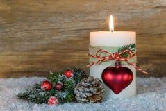 与圣诞节心脏装饰的明亮的灼烧的蜡烛在雪 库存图片