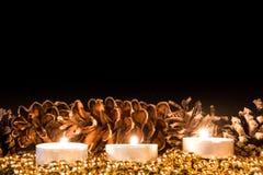 与圣诞节杉木锥体的蜡烛在大气光 免版税库存图片