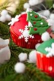 与圣诞节标志的红色杯形蛋糕 免版税图库摄影