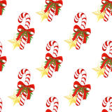 与圣诞节棒棒糖、金黄星、弓、霍莉叶子和莓果的水彩手拉的假日样式 无缝 免版税库存图片