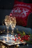 与圣诞节汽酒玻璃的明信片在红色和白色的手工制造盘子绣了有鹿的枕头 图库摄影