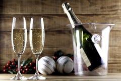 与圣诞节球和冰桶的两块香槟玻璃 免版税库存图片