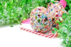 与圣诞节球和棒棒糖的绿色闪亮金属片 库存照片