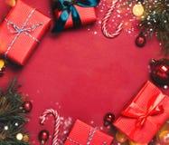 与圣诞节球的圣诞节红色背景和提出用落在他们的糖果和雪 图库摄影