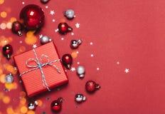 与圣诞节球的圣诞节红色背景和提出用落在他们的糖果和雪 免版税库存照片