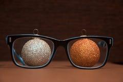 与圣诞节球的玻璃在木背景 银和金黄 免版税库存图片