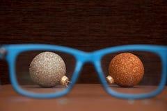 与圣诞节球的玻璃在木背景 免版税库存照片
