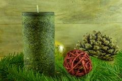 与圣诞节球的绿色蜡烛和冷杉在一个土气委员会分支 免版税库存照片