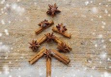 与圣诞节由香料肉桂条、茴香星和蔗糖做的杉树的圣诞卡在土气木背景 库存照片