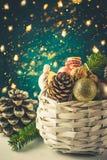 与圣诞节的白色柳条筐装饰金黄球,杉木锥体,坚果,礼品包装材料丝带 看板卡圣诞节问候 库存照片