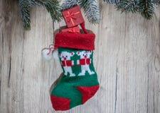 与圣诞节磁带的礼物有在木后面的一只羊毛红色袜子的 免版税图库摄影