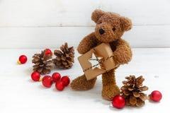 与圣诞节礼物、锥体和红色球的逗人喜爱的玩具熊在a 免版税库存图片