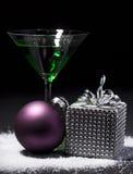与圣诞节礼物包裹和圣诞节球的绿色鸡尾酒 免版税库存图片